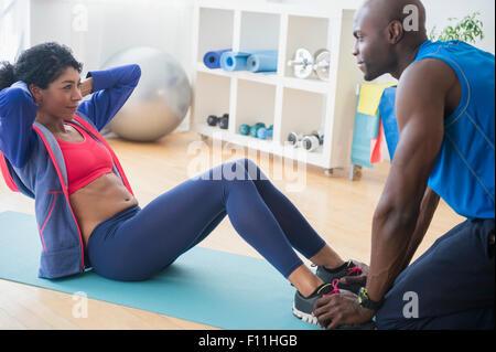 Woman doing sit-ups avec trainer in gym Banque D'Images