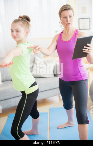 Caucasian mother and daughter practicing yoga with digital tablet Banque D'Images