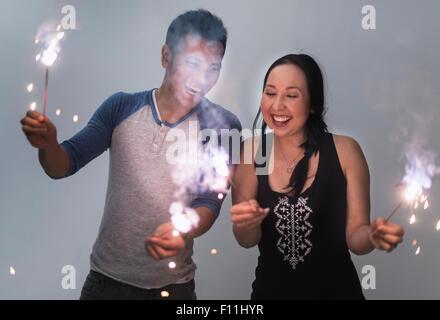 Smiling couple jouant avec les cierges magiques Banque D'Images