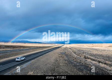 Portrait de voiture roulant à arc-en-ciel sur la route à distance Banque D'Images