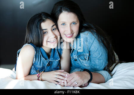 Hispanic mother and daughter smiling on bed Banque D'Images