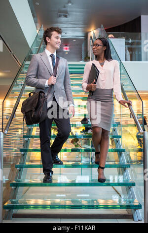Business people talking on staircase in office Banque D'Images