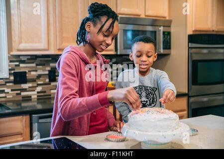 Frère et sœur noire decorating cake in kitchen Banque D'Images