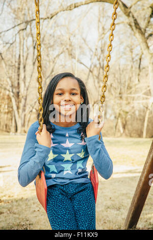 Black girl sitting on swing Banque D'Images