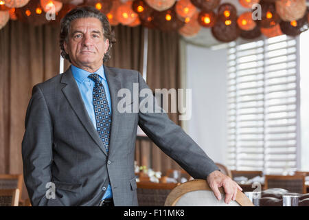 Businessman standing in dining room Banque D'Images