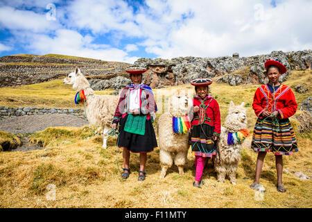 La mère et les enfants hispaniques debout avec des lamas in rural landscape Banque D'Images