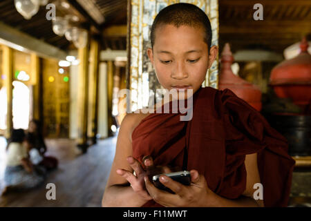 Moine asiatique en formation à l'aide de téléphone cellulaire à l'intérieur Banque D'Images