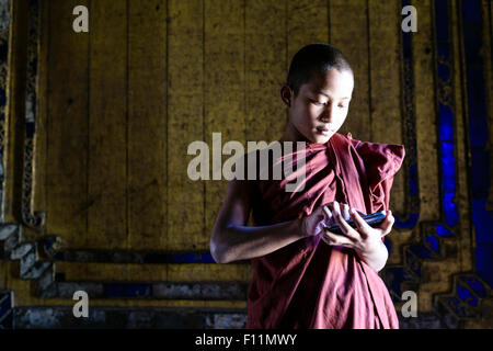 Moine asiatique en formation using cell phone in temple Banque D'Images