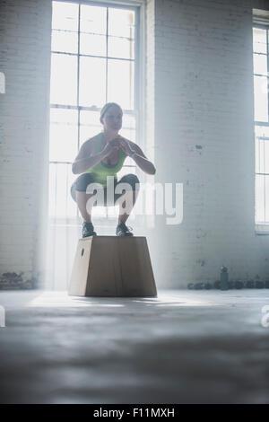 Accroupi sur l'athlète dans la plate-forme de sport Banque D'Images