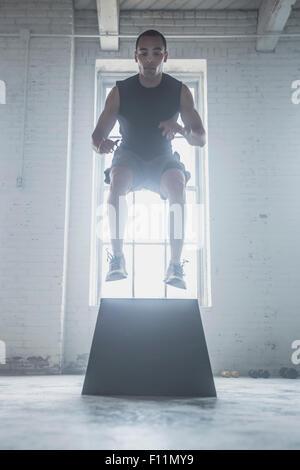 Le saut de l'athlète sur la plate-forme Banque D'Images