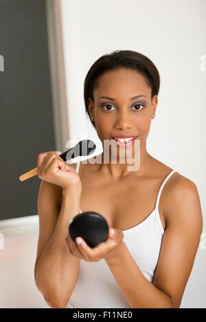 Mixed Race woman applying makeup Banque D'Images