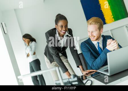 Business people talking et souriant dans un bureau en face d'un ordinateur portable