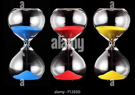 Trois sabliers avec du sable coloré, bleu, rouge et jaune,fonctionnant par les ampoules de verre mesurant le temps Banque D'Images