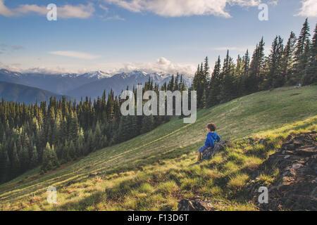 Garçon assis sur un rocher sur une montagne Banque D'Images