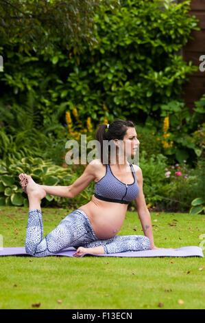Pregnant woman doing yoga dans le jardin Banque D'Images