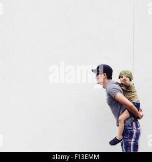 Père de donner son fils un piggyback ride Banque D'Images