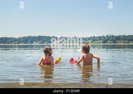 Vue arrière d'un garçon et une fille assise dans l'eau du lac peu profond Banque D'Images