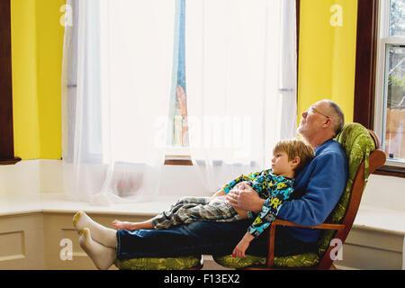 Garçon assis sur les genoux de son grand-père relaxing Banque D'Images