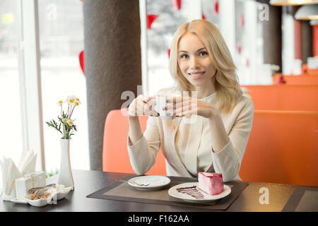 Très beau, heureux, jeune femme, s'asseoir dans un café et manger un dessert avec café ou thé, portrait horizontal Banque D'Images