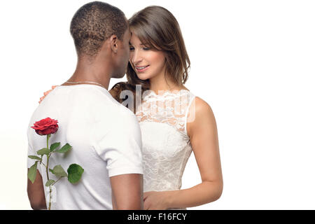 Jeune homme romantique avec une jolie femme se cachant une rose rouge dans son dos alors qu'il se prépare à surprendre Banque D'Images