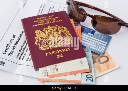 Assurance voyage passeport britannique et de l'argent monnaie documents carte d'assurance maladie et des lunettes Banque D'Images