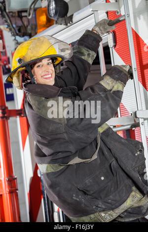 Heureux firewoman debout sur camion à la caserne Banque D'Images
