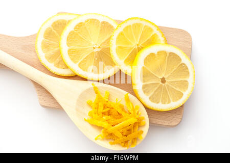 Le zeste de citron et des tranches de citrons sur une planche à découper, les ingrédients pour un dessert Banque D'Images