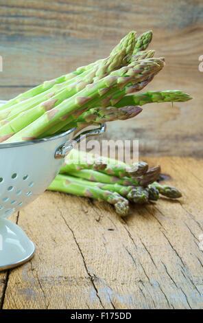 Les asperges vertes dans une passoire blanche sur une table en bois rustique Banque D'Images