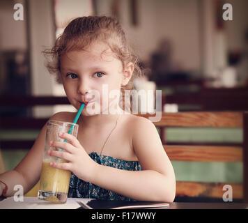 Pensée Cute kid girl boire du jus de café avec regard sérieux. Closeup portrait Banque D'Images