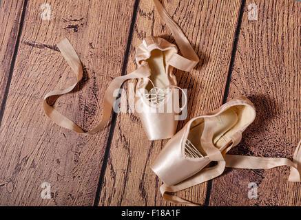Des chaussons de ballet s'allonger sur le sol en bois. Vintage. Le concept de ballet classique et la danse contemporaine. Banque D'Images