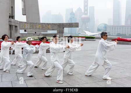 Le Tai Chi en groupe exercices de comparaison de près de Shanghai Bund en vue de la skyline de Pudong, qui est camouflée Banque D'Images