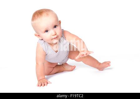 Studio shot of baby boy jouant sur le sol à la recherche de l'appareil photo. Banque D'Images