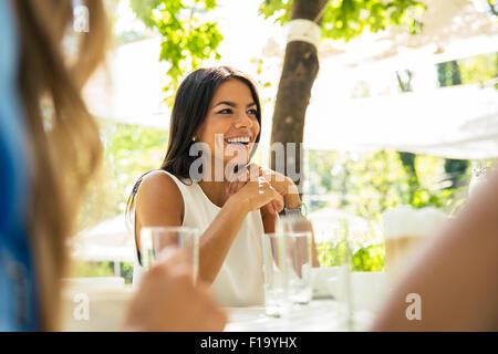 Portrait d'une femme riant assis à la table de restaurant en plein air