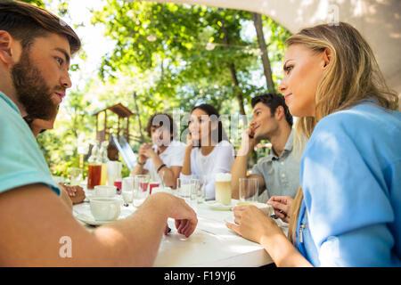 Un groupe d'amis heureux assis à la table de restaurant en plein air Banque D'Images