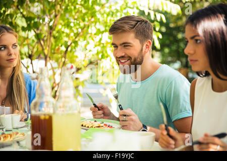 Le groupe d'un smiling friends sitting in outdoor restaurant Banque D'Images