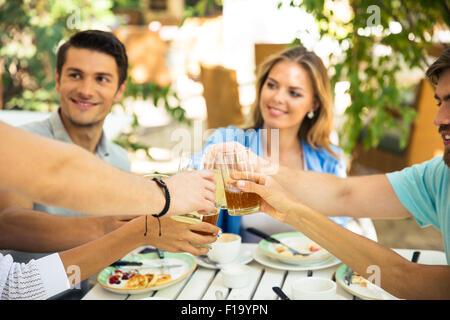 Happy friends making toast autour de table à dîner dans le restaurant de plein air Banque D'Images