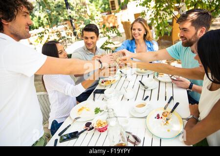 Un groupe de jeunes amis faire toast autour de table à dîner dans le restaurant de plein air Banque D'Images