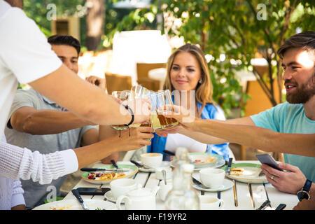 Un groupe d'amis joyeux toasts autour de table à dîner dans le restaurant de plein air Banque D'Images