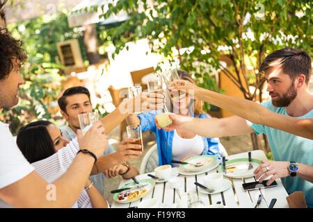 Un groupe d'amis autour de la table toast à dîner dans le restaurant de plein air Banque D'Images