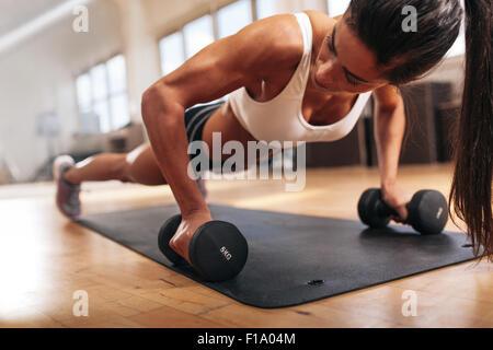 Gym woman doing push-up exercice avec haltère. Des femmes faisant l'entraînement Crossfit.