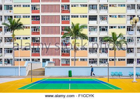 Homme marchant passé Choi Hung Estate, un des plus vieux quartiers de Hong Kong, quartier de Wong Tai Sin, Kowloon, Banque D'Images