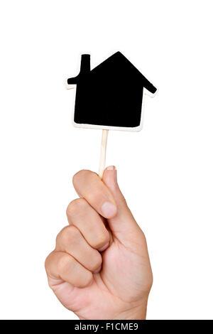 Libre de la main d'un jeune homme tenant un blank chalkboard dans la forme d'une maison, sur un fond blanc. Banque D'Images
