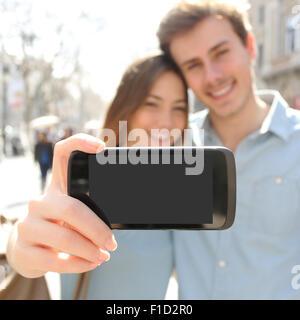Heureux couple ou des amis de prendre une photo avec un selfies smart phone et montrant un écran vierge à l'appareil Banque D'Images