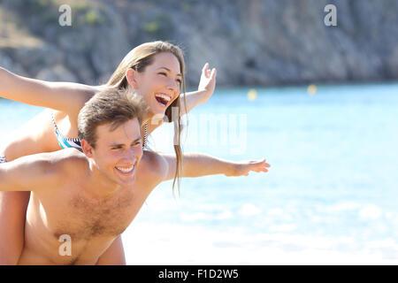 Heureux couple romantique jouant sur la plage sur vacances d'été Banque D'Images