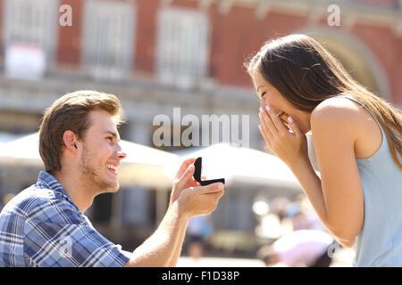 Proposition dans la rue avec un homme demandant à se marier à sa petite amie heureuse Banque D'Images
