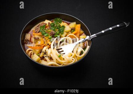 Soupe aux nouilles Lagman ouzbeks sur noir, vue du dessus Banque D'Images