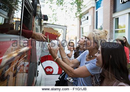 Les clients recevant de la nourriture à l'extérieur de camion alimentaire Banque D'Images