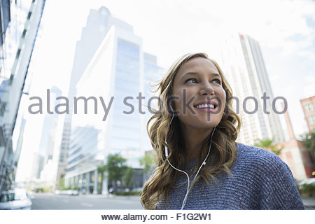 Smiling businesswoman listening to headphones in city Banque D'Images