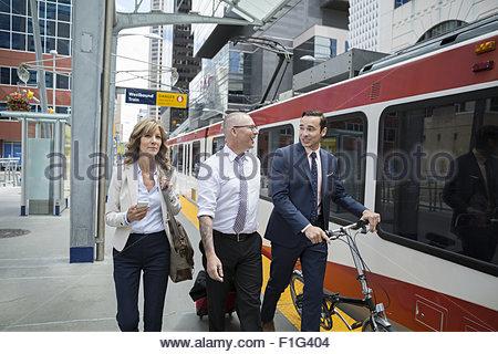 Les gens d'affaires à marcher le long de la plateforme de la gare de train Banque D'Images