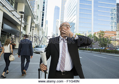 Sifflement businessman hailing taxi on city street Banque D'Images